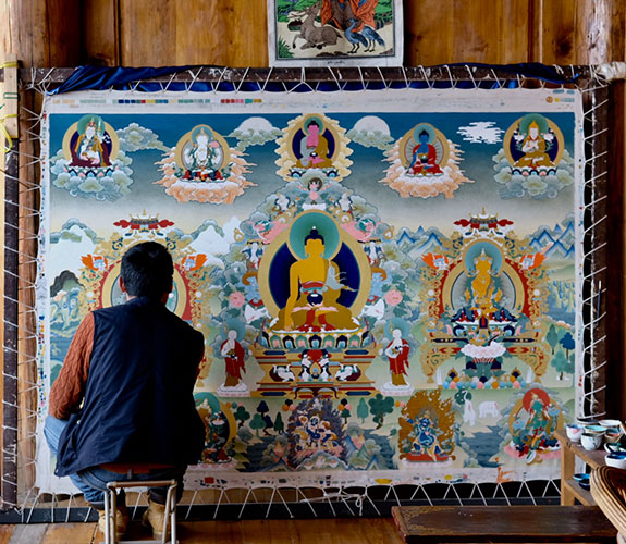 a Thangka artist is painting