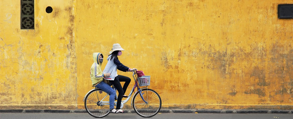 Two girls riding a bike in the Old Quarter of Hanoi